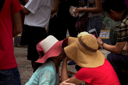 GRAND PALACE, BANGKOK, THAILAND, 26 SEPTEMBER 2014: Two Chinese tourists share an intimate moment while visiting the Grand Palace in Bangkok.