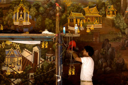GRAND PALACE, BANGKOK, THAILAND, 26 SEPTEMBER 2014: A painter works on restoring a mural painting tour at the Grand Palace in Bangkok. 報道画像