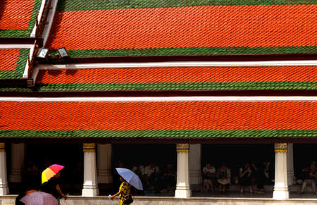 GRAND PALACE, BANGKOK, THAILAND, 26 SEPTEMBER 2014: A Chinese tour group seeks shade against the hot sun under the roof of a building at the Grand Palace in Bangkok