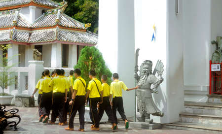 WAT PHO, BANGKOK, THAILAND, 26 SEPTEMBER 2014: A group of students on a school trip exit a building after viewing the Sleeping Buddha at Wat Pho. 報道画像