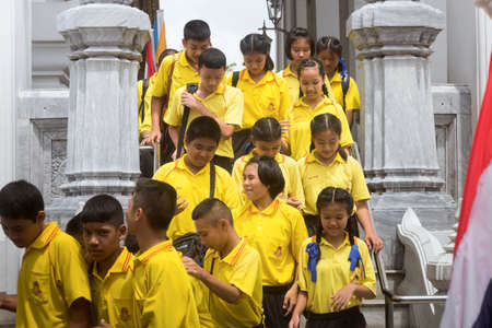 wat pho: WAT PHO, BANGKOK, THAILAND, 26 SEPTEMEBER 2014: Thai students on a school trip exit a building after viewing the Sleeping Buddha at Wat Pho