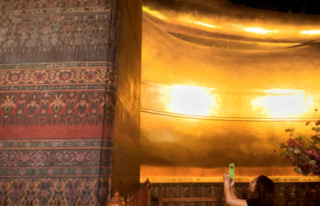 WAT PHO, BANGKOK, THAILAND, 26 SEPTEMBER 2014: A Thai tourist snapshots a photo whilst standing under Wat Pho\