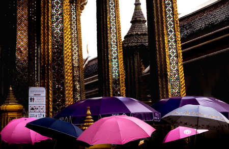 congregate: GRAND PALACE, BANGKOK, THAILAND, 26 SEPTEMBER 2014: A Chinese tour group uses umbrellas to shield against the hot sun at the Grand Palace in Bangkok