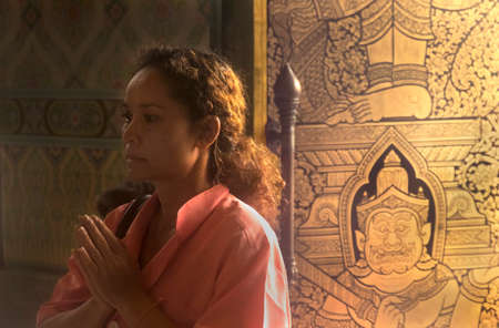 GOLDEN BUDDHA TEMPLE, BANGKOK, THAILAND, 28 SEPTEMBER 2014: A Thai woman says a prayer to the  Gold Buddha during a visit