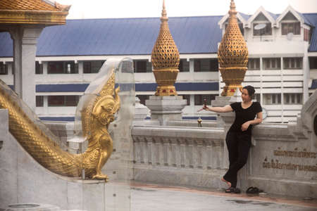 GOLDEN BUDDHA TEMPLE, BANGKOK, THAILAND, 28 SEPTEMBER 2014: A Chinese tourist takes a selfie with her smart phone at the Golden Buddha Temple