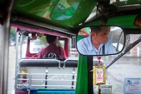 BANGKOK, THAILAND, 28 SEPTEMBER 2014: A tuk-tuk driver in Bangkok waits in front of another tuk-tuk at a traffic stop