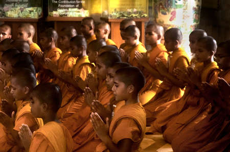 GOLDEN BUDDHA TEMPLE, BANGKOK, THAILAND, 28 SEPTEMBER 2014: A group of novice monks from the Meditation Education Training Treatment Academy (METTA) in India pray to the Golden Buddha during a visit 報道画像