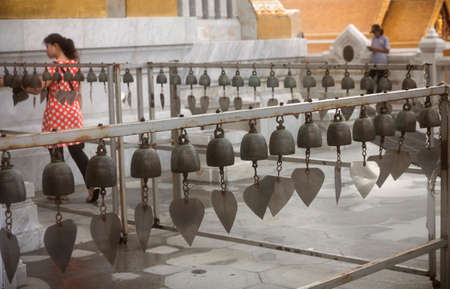 GOLDEN BUDDHA TEMPLE, BANGKOK, THAILAND, 28 SEPTEMBER 2014: During a visit, a Thai woman walks past rows of temple bells at the Golden Buddha Temple