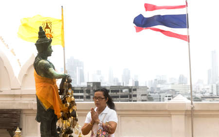 TEMPLE OF THE GOLDEN MT., BANGKOK, THAILAND, 28 SEPTEMBER 2014: Two flags billow in the wind over a woman praying at the top of the Golden Mt. Temple
