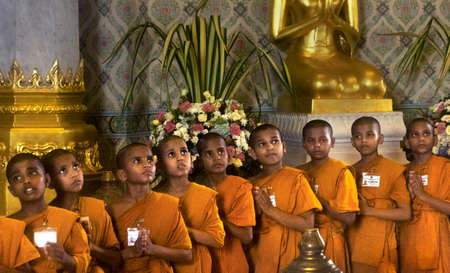 GOLDEN BUDDHA TEMPLE, BANGKOK, THAILAND, 28 SEPTEMBER 2014: A group of novice monks from the Meditation Education Training Treatment Academy (METTA) in India pray to the Gold Buddha during a visit