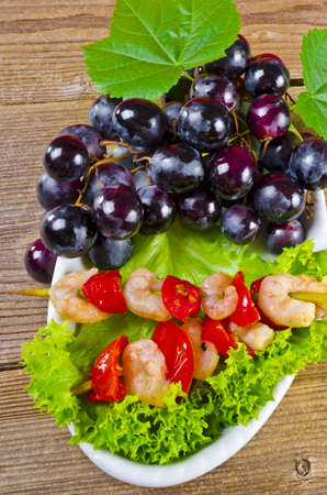 Grilled shrimp sticks with bunches of grapes, tomatoes and green salad photo