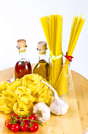 homemade pasta, cloves of garlic, cherry tomatoes and bottles of olive oil photo