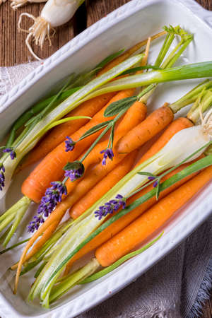 plate: Young carrots and spring onions prepared for baking