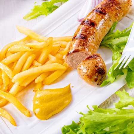 delicious grilled bratwurst with fries and mustard Stock Photo