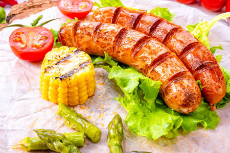 grilled krakauer sausage with boiled corn and green salad Standard-Bild