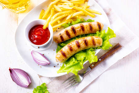 grilled bratwurst with chips and cold beer Stock Photo