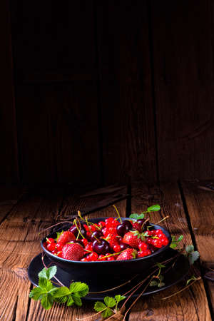 Bowl with different fruits such as strawberry, red currant, and cherry.