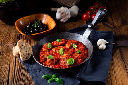 Baked mini meatballs in tomato sauce with basil Imagens