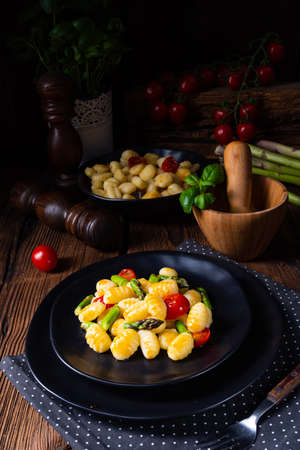 crispy gnocchi with roasted asparagus and tomatoes Banque d'images