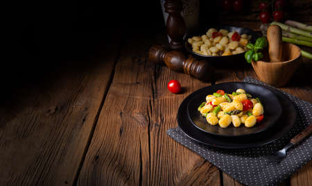 crispy gnocchi with roasted asparagus and tomatoes Stockfoto