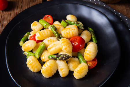 crispy gnocchi with roasted asparagus and tomatoes Foto de archivo
