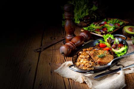 Pork steak with mushrooms and buckwheat groats and mango salad Stock Photo