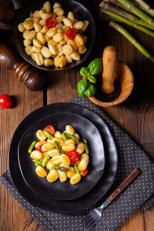 crispy gnocchi with roasted asparagus and tomatoes Фото со стока
