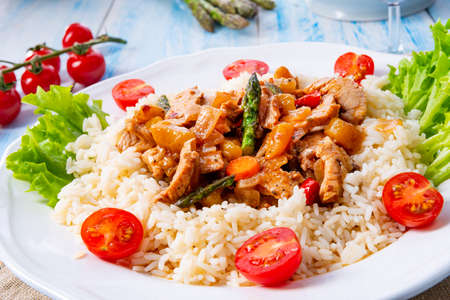 Turkey fricassee on rice with asparagus and paprika