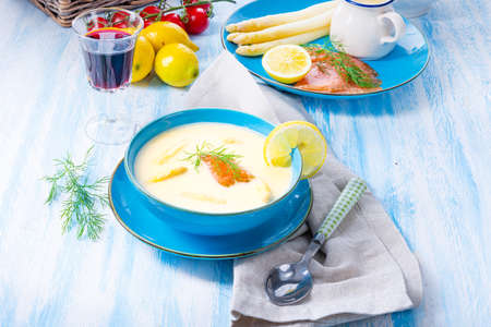 Cream of asparagus soup with salmon rolls and dill