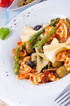 colorful farfalle with green asparagus olives and parma ham Фото со стока
