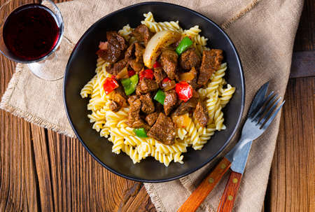 Fussili noodle with klaschise spicy goulash and paprika Imagens