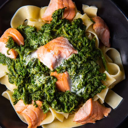 pappardelle pasta with creamed spinach and fried salmon Foto de archivo - 129789524