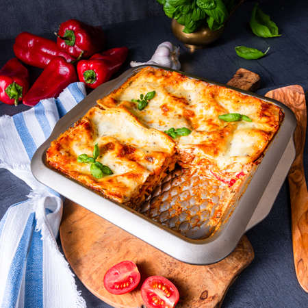 rustic spicy lasagne with basil on the tin. Foto de archivo - 129789525