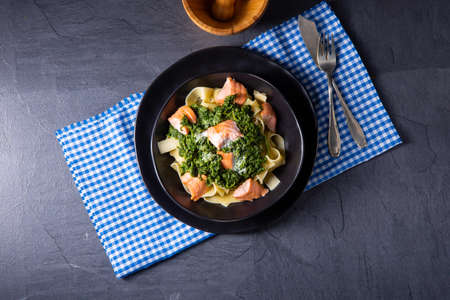 pappardelle pasta with creamed spinach and fried salmon Foto de archivo - 129789647