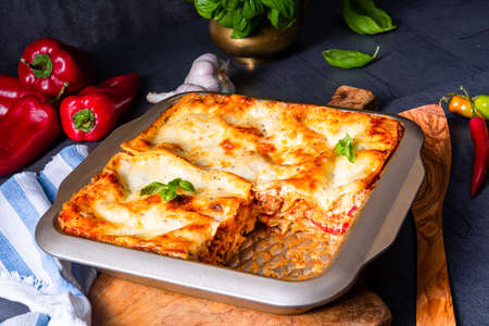 rustic spicy lasagne with basil on the tin. Foto de archivo - 129789650