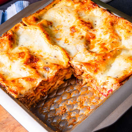 rustic spicy lasagne with basil on the tin.