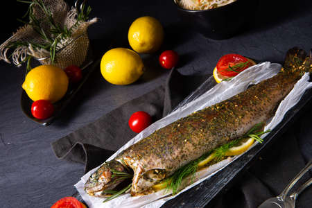 baked trout with herb filling and tomatoes Stockfoto - 130049314