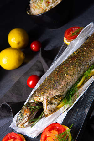 baked trout with herb filling and tomatoes Фото со стока