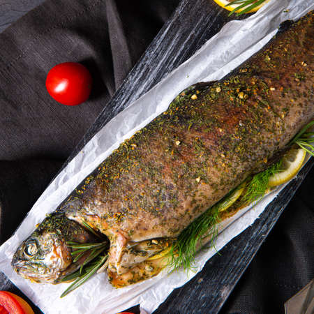 baked trout with herb filling and tomatoes Stock Photo