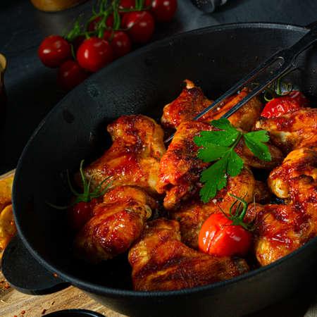 Spicy chicken wings in honey with potato wedges Foto de archivo