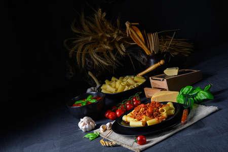 Rigatoni pasta with Bolognese sauce and fresh basil Stock Photo