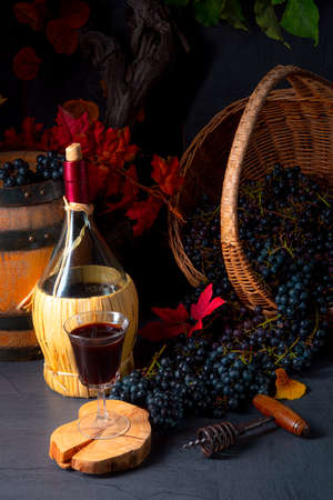 Grapes in the basket with wine and tree leaves Banque d'images