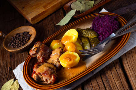 Rustic Snirtjebraten with red cabbage and cucumber