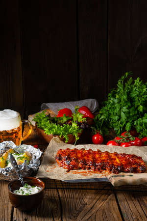Spicy spare ribs with baked potatoes and sour cream
