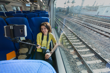 Young woman making selfies with smartphone during traveling in train sitting near window wideangle portrait 免版税图像