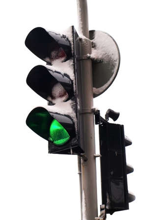 Frozen icy isolated traffic light with snow on it and green light lit