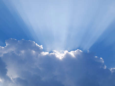 Pure blue sky with clouds and sunrays photo
