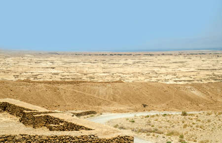 judean desert: Judean desert and ancient Roman fortifications near Masada fortress in Israel. Road among stone dunes and hills in Israel desert