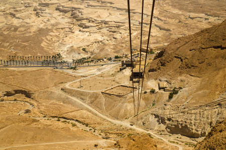 judaean desert: Cable car track, moving down from Masada fortress to Judean desert Israel. Ancient Roman fortifications are seen at the bottom of the mountain. Legendary Middle East places for tourists Stock Photo