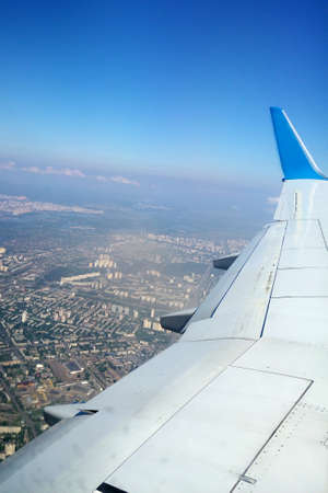 viewport: Plane wing with a city under it. Metal wings of a flying plane Stock Photo